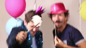Happy male friends dancing with props in photo booth stock footage