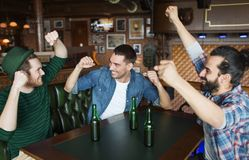 Happy male friends drinking beer at bar or pub. People, friendship and st patricks day concept - happy male friends drinking bottled beer and and celebrating at stock image