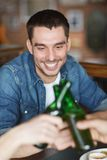 Happy male friends drinking beer at bar or pub. People, leisure, celebration, friendship and bachelor party concept - happy male friends drinking beer and royalty free stock photography