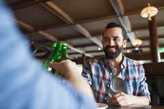 Happy male friends drinking beer at bar or pub. People, leisure, celebration, friendship and bachelor party concept - happy male friends drinking beer and stock photography