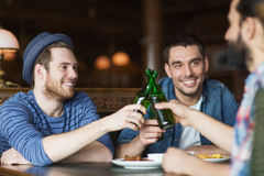 Happy male friends drinking beer at bar or pub. People, leisure, celebration, friendship and bachelor party concept - happy male friends drinking beer and stock photo
