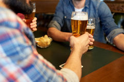 Happy male friends drinking beer at bar or pub. People, leisure, drinks and celebration concept - happy male friends drinking beer at bar or pub stock images