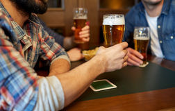 Happy male friends drinking beer at bar or pub. People, leisure, drinks and celebration concept - happy male friends drinking beer at bar or pub royalty free stock images