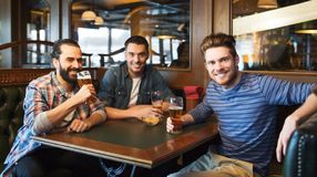 Happy male friends drinking beer at bar or pub. People, leisure, friendship and and bachelor party concept - happy male friends drinking beer at bar or pub royalty free stock photo