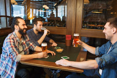 Happy male friends drinking beer at bar or pub. People, leisure, friendship and and bachelor party concept - happy male friends drinking beer at bar or pub royalty free stock photography
