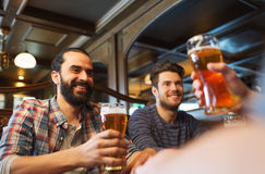 Happy male friends drinking beer at bar or pub. People, leisure, friendship and and bachelor party concept - happy male friends drinking beer at bar or pub royalty free stock images