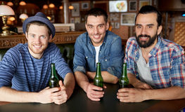 Happy male friends drinking beer at bar or pub. People, leisure, friendship and bachelor party concept - happy male friends drinking bottled beer at bar or pub royalty free stock image