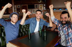 Happy male friends drinking beer at bar or pub. People, leisure, friendship and bachelor party concept - happy male friends drinking bottled beer and having fun stock photos