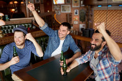 Happy male friends drinking beer at bar or pub. People, leisure, friendship and bachelor party concept - happy male friends drinking bottled beer and having fun royalty free stock images