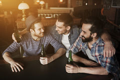 Happy male friends drinking beer at bar or pub. People, leisure, friendship and bachelor party concept - happy male friends drinking bottled beer and hugging at Royalty Free Stock Photos