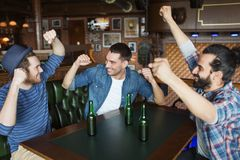 Happy male friends drinking beer at bar or pub. People, leisure, friendship and bachelor party concept - happy male friends drinking bottled beer and raised stock photo