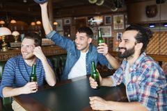 Happy male friends drinking beer at bar or pub. People, leisure, friendship and bachelor party concept - happy male friends drinking bottled beer and raised Stock Photography