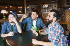Happy male friends drinking beer at bar or pub Stock Image