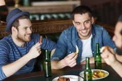 Happy male friends drinking beer at bar or pub. People, leisure, friendship and bachelor party concept - happy male friends drinking bottled beer and talking at royalty free stock photo
