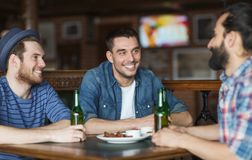 Happy male friends drinking beer at bar or pub. People, leisure, friendship and bachelor party concept - happy male friends drinking bottled beer and talking at royalty free stock images
