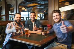 Happy male friends drinking beer at bar or pub. People, leisure, friendship and and bachelor party concept - happy male friends drinking beer and showing thumbs stock photography