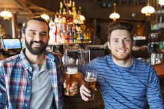 Happy male friends drinking beer at bar or pub. People, leisure, friendship and bachelor party concept - happy male friends drinking beer and talking at bar or stock photos