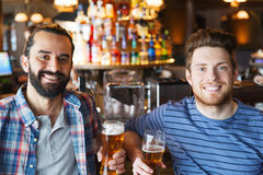 Happy male friends drinking beer at bar or pub. People, leisure, friendship and bachelor party concept - happy male friends drinking beer and talking at bar or stock photography