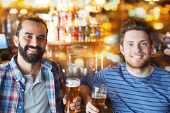 Happy male friends drinking beer at bar or pub. People, leisure, friendship and bachelor party concept - happy male friends drinking beer and talking at bar or stock photo