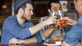 Happy male friends drinking beer at bar or pub. People, leisure, friendship and celebration concept - happy male friends drinking beer, eating bread snack and stock video