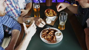 Happy male friends drinking beer at bar or pub stock footage