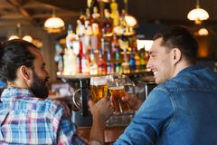 Happy male friends drinking beer at bar or pub. People, leisure, friendship, communication and bachelor party concept - happy male friends drinking beer and stock photo