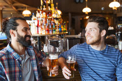 Happy male friends drinking beer at bar or pub. People, leisure, friendship, communication and bachelor party concept - happy male friends drinking beer and royalty free stock images