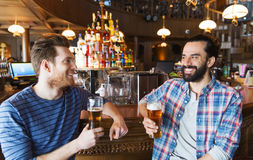 Happy male friends drinking beer at bar or pub. People, leisure, friendship, communication and bachelor party concept - happy male friends drinking beer and royalty free stock photos