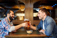 Happy male friends drinking beer at bar or pub. People, leisure, friendship and party concept - happy male friends drinking draft beer at bar or pub and clinking royalty free stock photos