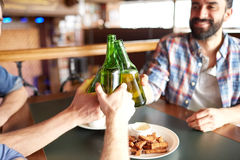 Happy male friends drinking beer at bar or pub. People, men, leisure, friendship and celebration concept - happy male friends drinking beer and clinking bottles stock images