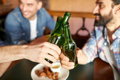Happy male friends drinking beer at bar or pub. People, men, leisure, friendship and celebration concept - happy male friends drinking beer and clinking bottles stock photography