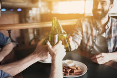 Happy male friends drinking beer at bar or pub. People, men, leisure, friendship and celebration concept - happy male friends drinking beer and clinking bottles Stock Photos