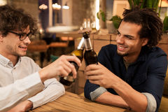 Happy male friends drinking beer at bar or pub. People, men, leisure, friendship and celebration concept - happy male friends drinking beer and clinking bottles stock image