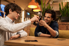 Happy male friends drinking beer at bar or pub. People, men, leisure, friendship and celebration concept - happy male friends drinking beer and clinking bottles royalty free stock photography
