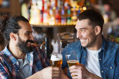 Happy male friends drinking beer at bar or pub. People, men, leisure, friendship and celebration concept - happy male friends drinking beer and clinking glasses stock photo