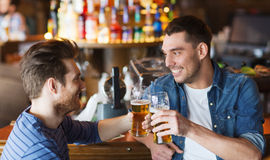 Happy male friends drinking beer at bar or pub Stock Photo