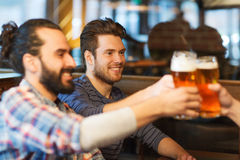 Happy male friends drinking beer at bar or pub. People, men, leisure, friendship and celebration concept - happy male friends drinking beer and clinking glasses royalty free stock image