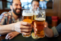 Happy male friends drinking beer at bar or pub. People, men, leisure, friendship and celebration concept - happy male friends drinking beer and clinking glasses stock photos