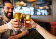 Happy male friends drinking beer at bar or pub. People, men, leisure, friendship and celebration concept - happy male friends drinking beer and clinking glasses stock image