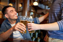 Happy male friends drinking beer at bar or pub. People, men, leisure, friendship and celebration concept - happy male friends drinking beer and clinking glasses royalty free stock photos