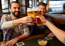 Happy male friends drinking beer at bar or pub. People, men, leisure, friendship and celebration concept - happy male friends drinking beer and clinking glasses stock images