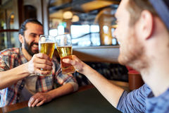 Happy male friends drinking beer at bar or pub. People, men, leisure, friendship and celebration concept - happy male friends drinking beer and clinking glasses royalty free stock images