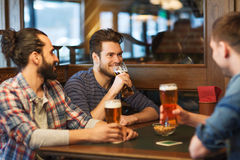 Happy male friends drinking beer at bar or pub. People, men, leisure, friendship and communication concept - happy male friends drinking beer at bar or pub royalty free stock photos