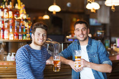Happy male friends drinking beer at bar or pub. People, men, leisure, friendship and communication concept - happy male friends drinking beer at bar or pub stock image