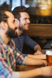 Happy male friends drinking beer at bar or pub. People, men, leisure, friendship and communication concept - happy male friends drinking beer at bar or pub stock images