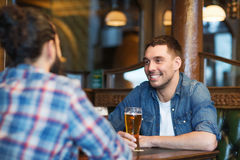 Happy male friends drinking beer at bar or pub. People, men, leisure, friendship and communication concept - happy male friends drinking beer at bar or pub royalty free stock photography