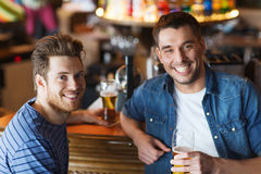 Happy male friends drinking beer at bar or pub. People, men, leisure, friendship and communication concept - happy male friends drinking beer at bar or pub stock photography