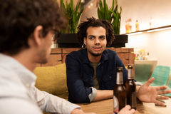 Happy male friends drinking beer at bar or pub. People, men, leisure, friendship and communication concept - happy male friends drinking bottled beer and talking stock image