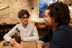 Happy male friends drinking beer at bar or pub. People, men, leisure, friendship and communication concept - happy male friends drinking bottled beer and talking stock photos