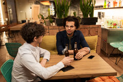 Happy male friends drinking beer at bar or pub. People, men, leisure, friendship and communication concept - happy male friends drinking bottled beer and talking stock photography